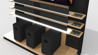 Lit shelves coordinate with product selections in this sound bar end cap display. TouchSelect panels provide volume controls for each product.